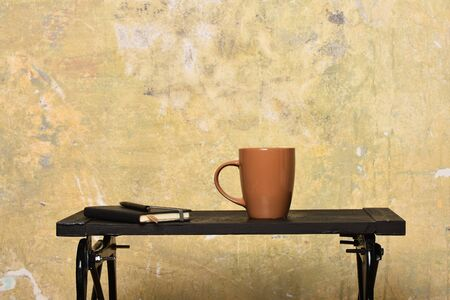 Diary with pen and new cup indoors. Tea or coffee on low black table in modern interior. Notebook with bookmark, pen and brown cup on table near wall. Time-management and making notes concept. 版權商用圖片
