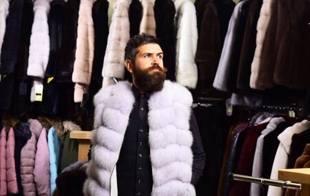 Man with beard and mustache wearing white fur coat.