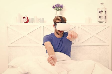 Conscious awakening. Return to reality. Man explore vr while relaxing in bed. Awakening from virtual reality. VR technology and future. VR communication. Exciting impressions. Gaming augmented space