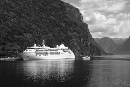 Cruise liner in sea port on mountain landscape in Flam, Norway. Holiday ship in sea harbor with green mountains. Cruise destination and travel. Summer vacation and holiday. Wanderlust and discovery.