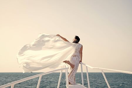 Honeymoon sea cruise. Things consider for wedding abroad. Wedding ceremony sea cruise. Bride adorable white wedding dress sunny day posing on boat or ship. Advice and tips from wedding abroad experts. 免版税图像 - 140257079