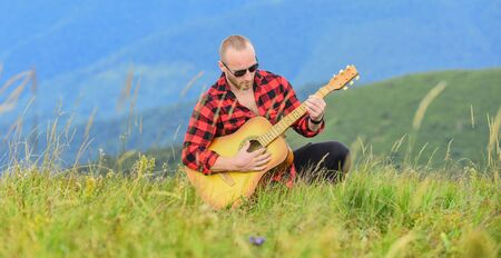 Keep calm and play guitar. Man with guitar on top of mountain. Acoustic music. Music for soul. Playing music. Sound of freedom. In unison with nature. Musician hiker find inspiration in mountains. Stock Photo