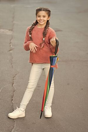 Girl child long hair ready meet fall weather with folded umbrella.