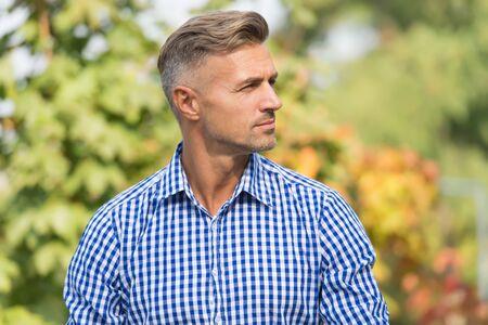 Schöner Mann mit stilvollem Haar im Freien