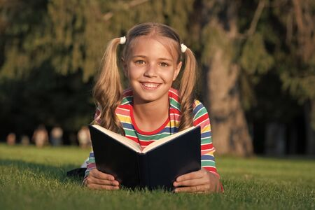 Cute reader read book on green grass.