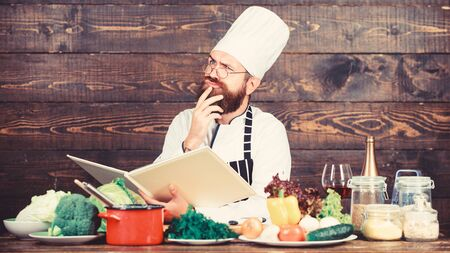 Culinary arts concept. Man learn recipe. Try something new. Cookery on my mind. Improve cooking skill. Book recipes. According to recipe. Man bearded chef cooking food. Guy read book recipes.