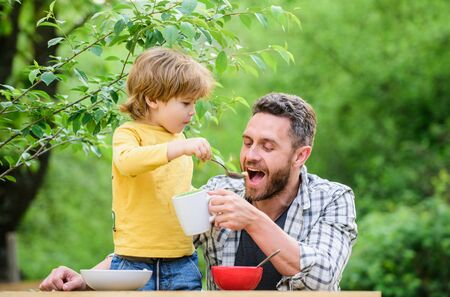 Menu for children. Family enjoy homemade meal. Food habits. Little boy with dad eating food nature background. Summer breakfast. Healthy food concept. Father son eat food and have fun. Feeding baby