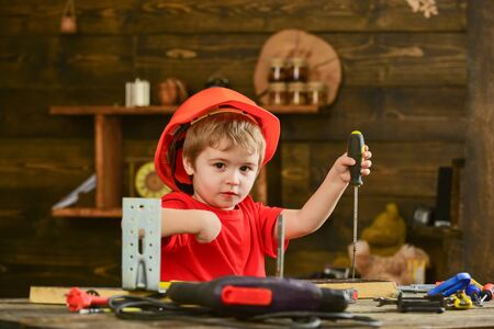 Handcrafting and workshop concept. Toddler on busy face plays with screwdriver at workshop. Child in helmet cute playing as builder or repairer, or handcrafting. Kid boy holds screwdriver tool.