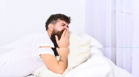 Man in shirt yawning while laying on bed, white wall and curtain on background. Sleepyhead concept. Macho with beard and mustache yawning, relaxing, having nap, rest. Guy on sleepy tired face yawning.