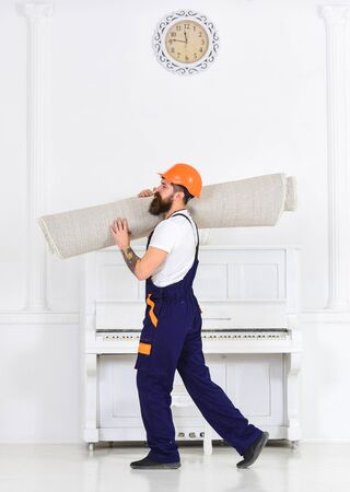 Relocating concept. Courier delivers furniture in case of move out, relocation. Loader wrapped carpet into roll. Man with beard, worker in overalls and helmet carries rolled carpet, white background.