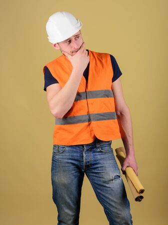 Engineer, architect, labourer, builder on thoughtful face holds old blueprints in hand. Engineering concept. Man, foreman in helmet, hard hat has doubts about building plan, ocher background.