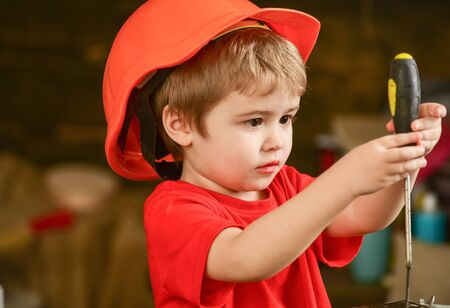 Closeup blond kid with screwdriver in workshop. Boy binding screws to wooden block. Concentrated child discovering new stuff Banco de Imagens