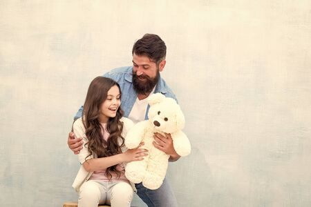 Giving soft toy teddy bear. Lovely father and kid. Father and daughter light background. Strengthening father daughter relationships. Child and dad best friends. Family relations. Fathers day concept 版權商用圖片