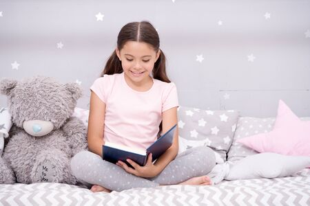 Dreaming big. Girl child in bed read book with teddy bear plush toy. Pleasant time in cozy bedroom. Girl kid cute pajamas relax and read book. Book about love. Favorite fairy tale. Literature hobby Standard-Bild