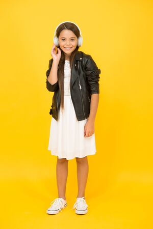 happy childhood concept. back to school. online karaoke singing. music in wireless earphones. trendy kid yellow wall. child listen to music in headset. small girl enjoy DJ music. music distribution