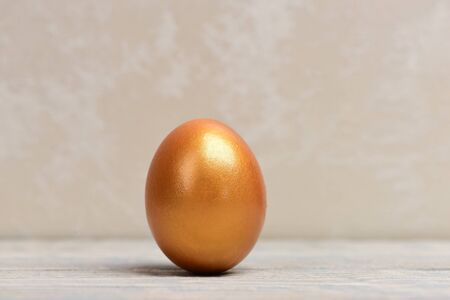traditional egg painted in golden metallic color on grey background, happy easter concept, luxury and success, birth and future life, business and finance, antique art and retirement Banco de Imagens