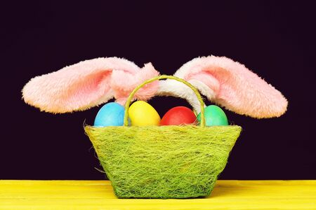 Easter bunny ears and basket filled with painted easter eggs on yellow wooden table isolated on black background. Easter and gift concept Imagens
