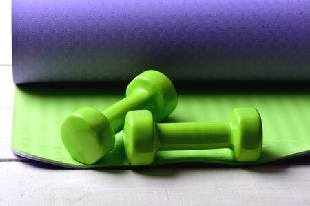 Dumbbells made of green plastic on green and purple texture background. Shaping and fitness equipment. Barbells lying on yoga mat, close up. Sports and healthy lifestyle concept