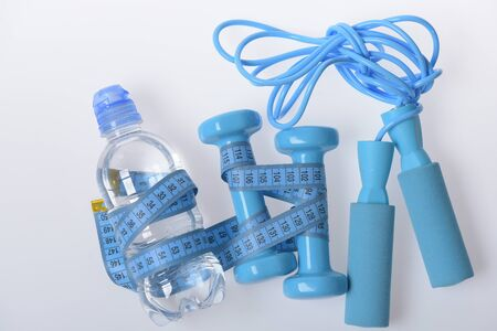 Fit shape and sport concept. Dumbbells, skipping rope in cyan color near water bottle on white background. Health and fitness symbols. Jump rope, water and barbells tied with blue measure tape 스톡 콘텐츠