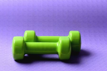 Shaping and fitness equipment. Barbells in small size on yoga mat, close up. Dumbbells made of green plastic on purple background. Healthy shape and sport concept 스톡 콘텐츠