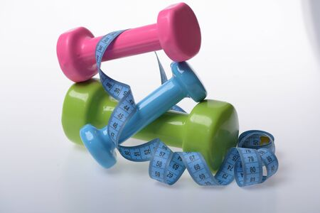 Dumbbells near blue rolled ruler on white background. Health regime and fitness symbols. Measure tape and pink, green and blue barbells on each other. Fit shape and sport concept