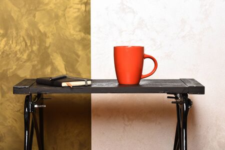 Cup of tea or coffee and diary on stylish background. Reading, writing and education concept. Cup of hot beverage and notebook on small table. Hot drink and notebook on low table near wall.
