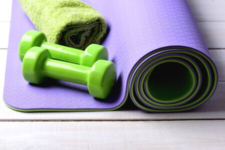 Shaping and fitness equipment. Dumbbells made of green plastic on light wooden background. Barbells near soft green towel lying on purple yoga mat. Sports and healthy lifestyle concept