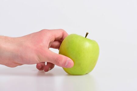Apple fruit isolated on light grey background. Apple in bright and juicy color. Male hand holds green apple. Vitamins and fitness concept.