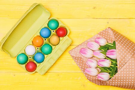 Egg hunt. Spring holiday. Holiday celebration, preparation. Tulip flower bouquet. Healthy and happy holiday. painted eggs in egg tray. Happy easter.