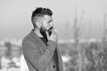 Cigarette tobacco harmful health influence. Smoking aesthetics. Smoking devices concept. Bearded hipster smoking outdoors. Device hide conceal smell of smoke. Handsome man smoke flying out of mouth