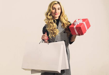 Real shopaholic. Present for her. Best gift ever. Blond curly hair. stylish girl with shopping bag. Beauty and fashion. woman look at red present box. Sexy business woman. Successful shopping