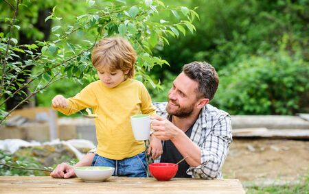 Healthy food concept. Father son eat food and have fun. Menu for children. Family enjoy homemade meal. Food habits. Little boy with dad eating food picnic yard nature background. Summer breakfast