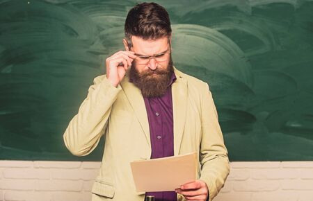 Prepare for test. Teacher bearded man hold documents chalkboard background. Teacher paperwork. School principal. Demanding teacher. Lecturer in classroom. Explaining theory. College and high school.
