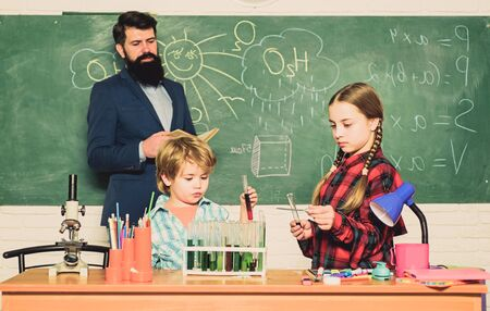 happy children teacher. back to school. kids in lab coat learning chemistry in school laboratory. doing experiments with liquids in chemistry lab. chemistry lab. Bad medical results