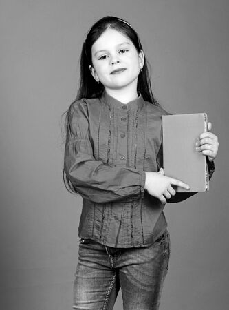 Girl hold book violet background. Kid show book. Book concept. Literature club. Development and education. Reading skill. Personal diary. Textbook presentation. Study and learn. Poetry author