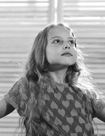 small girl with thoughtful look. look in future. dreaming. lost in fairytale. little day dreamer. little girl with long hair. healthy child. childhood happiness. kid beauty. pure look