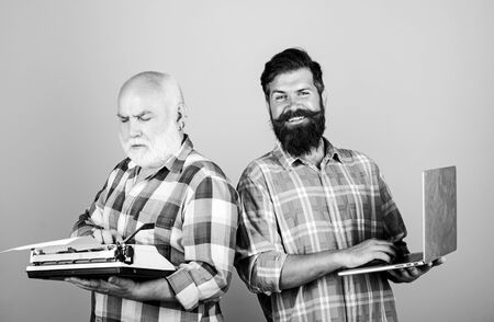 Digital technologies. bearded men. Vintage typewriter. technology battle. Modern life. father and son. family generation. retro typewriter vs laptop. New technology. youth vs old. business approach Stockfoto