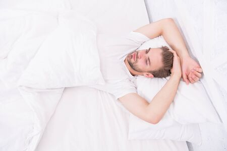 Tips promoting healthful sleep habits. Handsome man relaxing in bed. Establish regular nightly sleep pattern. Practice calming activities such as meditation before going to bed. Healthy sleep concept. Foto de archivo