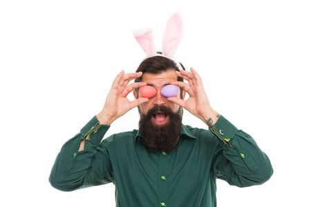 Mr bunny hop. Hipster hold eggs as glasses. Easter bunny bringing eggs. Bearded man wear bunny ears. Funny bunny rabbit. Spring and fertility. Egg rolling. Easter celebration.