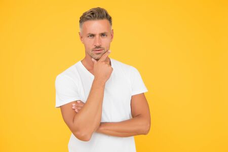 Thinking about shaving beard off. Serious guy touch beard hair yellow background. Unshaven man with stubble beard and mustache. Mens grooming products. Hair salon. Barbershop, copy space