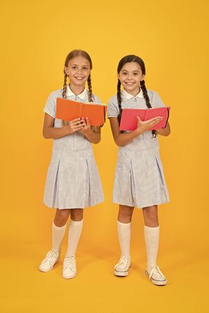 Childrens literature. small girls hold workbook or notepad. encyclopedia book for children. small girls love reading. old school. happy friends in retro uniform. vintage kid fashion. back to school