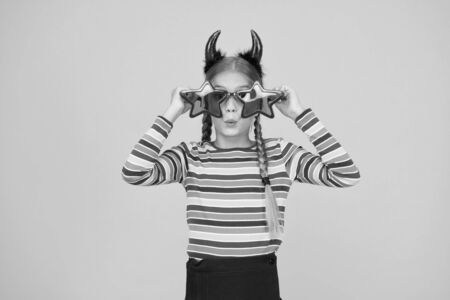 Crazy is her name. Crazy halloween child yellow background. Party girl with crazy look. Fashion kid wear red devil horns and star shaped glasses. Crazy holiday mood. Holiday season. Fancy beauty 写真素材