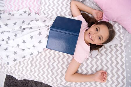 Fantasy literature. Happy girl read fantasy book in bed. Small kid enjoy reading. Fantasy and fantastic fiction. Developing child fantasy and imagination. Imaginary world. Fairy tale. Bedtime reading Archivio Fotografico