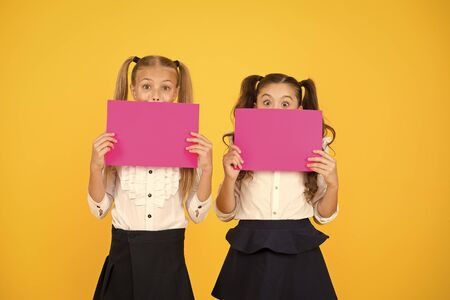 Drawing attention. Happy kids holding empty sheets of paper. Little kids smiling with pink drawing papers. Small kids smiling with blank advertisement posters. Cute kids advertising, copy space Banque d'images - 141416766