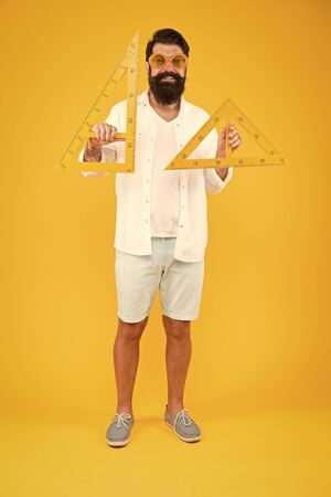 Triangle is the most important shape in engineering. Engineer using triangles for making engineering drawings. Bearded man teaching engineering discipline. Engineering and design