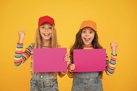 Your advertising wins. Happy small children showing pink paper sheets for advertising on yellow background. Little girl advertising product or event. Winning advertising solutions for you, copy space