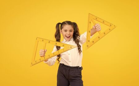 Exploring the properties of triangles in the lesson. Cute girl holding triangles for lesson in technical drawing. Little child ready for geometry lesson. Using measuring instruments at school lesson Banque d'images - 141419469