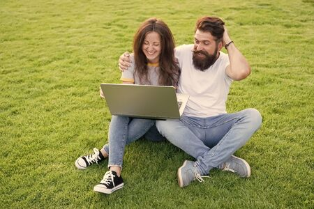 Modern technologies. Online work. Couple students green meadow. Laptop online communications. Surfing internet. Happy couple spend leisure outdoors with laptop. Man and girl looking laptop screen