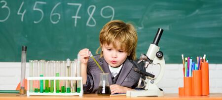 School education. Explore biological molecules. Toddler genius baby. Technology and science concept. Boy near microscope and test tubes in school classroom. Kid study biology and chemistry in school
