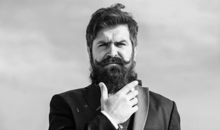Bearded man. Future success. Male formal fashion. brutal caucasian hipster with moustache. Businessman against the sky. Mature hipster with beard. Bearded man touch beard. Man with beard outdoor Banque d'images